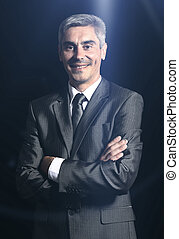 Closeup of a smiling senior man isolated over black...