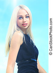 Beautiful woman with long straight blond hair. Fashion model posing at studio