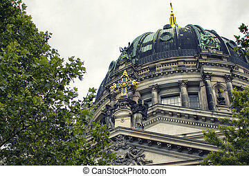 Close up view of histrorical, golden crosss sign on top of Berliner Dom. Majestic 1800s cathedral with an organ with 7,000 pipes, plus royal tombs & a dome for city views.