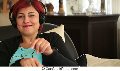 Woman with headphone dancing - Happy middle aged woman with...