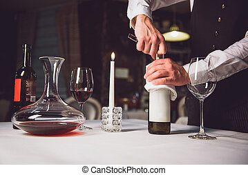 Opening bottle of white wine - Waiter is holding flask with...