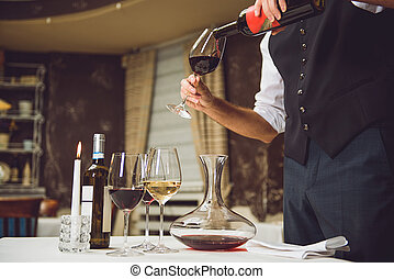 Waiter pouring scarlet wine into glass - Man is standing...