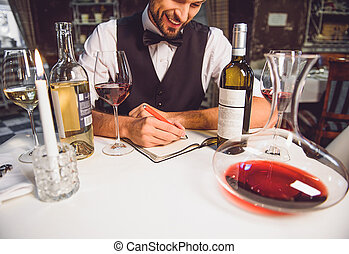 Wine critic is in good mood - Smiling man is sitting at...