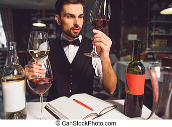 Wine critic absorbedly looking at glasses