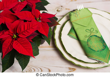 Christmas dinner with red star Christmas flower poinsettia on rustic wooden background