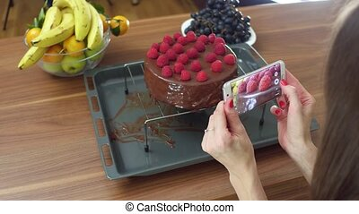 Young woman taking photos of her freshly cooked raspberry...