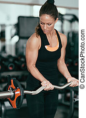 Woman exercising in gym with barbell weights