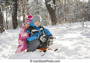 Winter in the woods a little boy and girl sitting on a sled.