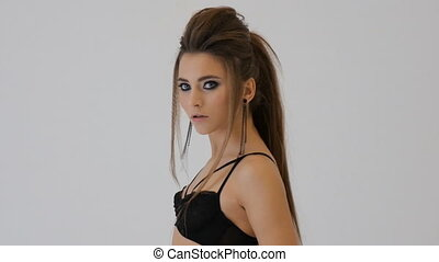Young European woman in black lingerie on photo session in the studio