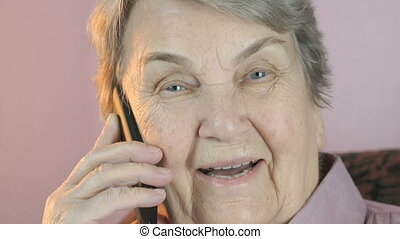Grandmother smiling talks on the mobile phone. Close up