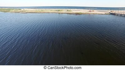 Shooting low over the bay and the sandy beach and the sea -...
