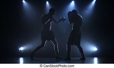 Two young sportsman are boxing in the studio. Slow motion
