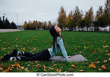 Beautiful girl stretching at the grass. Sporty young...