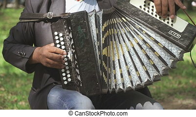 Adult man sitting on a chair plays the accordion outdoors in...