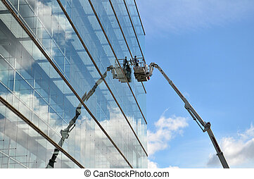 The man during the cleaning of big glass building.