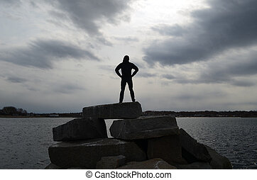 Guy Silhouetted in a Super Hero Pose on a Rock Jetty - Guy...