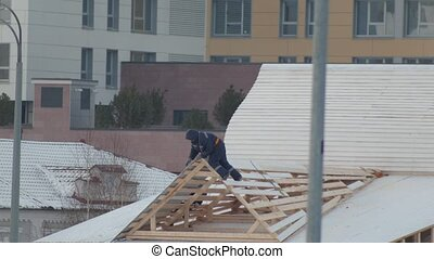 Construction workers install wooden roof on a house. Snow...