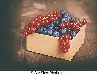 blue berries and Red currant in box on wooden table