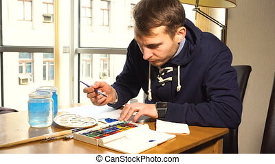 Artist drawing a painting - Artist working on painting with...