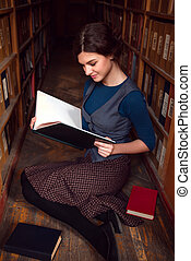 Student girl with open book in university library. - Student...