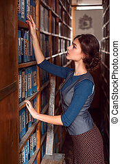 Woman taking a book from bookshelf. - Young woman at the...