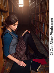 University student sitting on a floor of library. -...