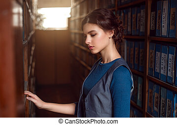 Young woman selecting book from library shelf. Knowledge,...