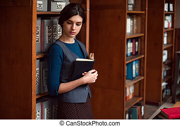 Girl with book in hands at the school library. - Young girl...