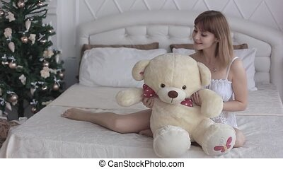 beautiful girl with toy on bed