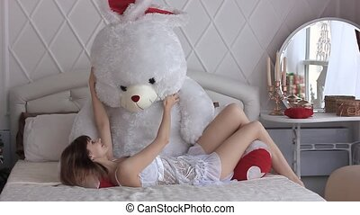 beautiful girl with toy on bed - Young Beautiful girl at...