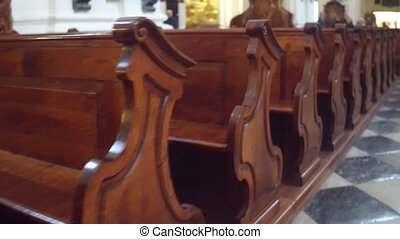 Rows of wooden benches in catholic church. 4K steadicam...