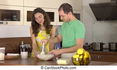 Man and woman cooking together. Stirring dough in a glass bowl. 4K steadicam shot