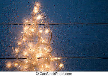 Christmas card with luminous festoon on empty wooden...