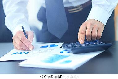 Businessman Using Calculator In Office