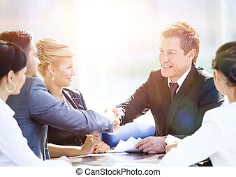 Business people shaking hands - Business colleagues sitting...