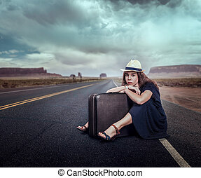 Young girl with luggage traveling hitchhiking. Rocky...