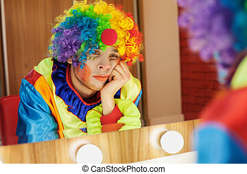 Circus clown looks in a mirror in makeup room. - Circus...