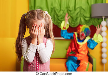 Girl playing hide and seek with a cheerful clown.