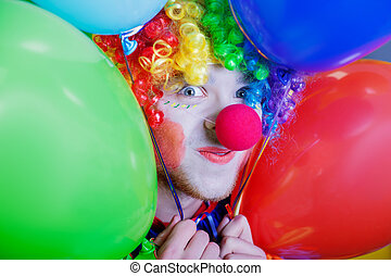 Clown with a bunch of colorful air balloons. - Smiling clown...