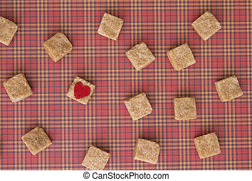 Brown sugar cubes with a red heart on one of them. Top view....
