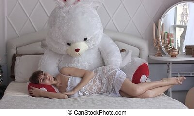 beautiful woman with toy on bed - Young Beautiful woman at...
