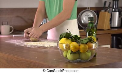 Man in green kneading pasta dough. 4K steadicam shot - Man...