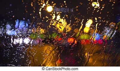 Wet the window with the background of the night city traffic view.