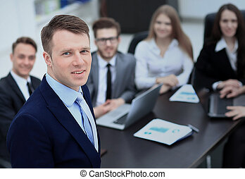 Successful business man standing with his staff in background at office