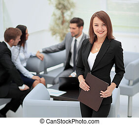 Successful business woman standing with her staff in background