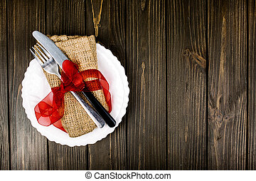 plate with cutlery and napkin lie on wooden surface