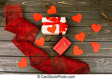 two gift boxes and red ribbon lying on a wooden surface