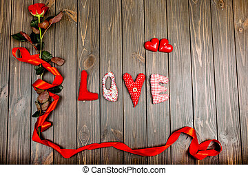 """the word """"love"""" and a red rose with a ribbon lie on wooden..."""