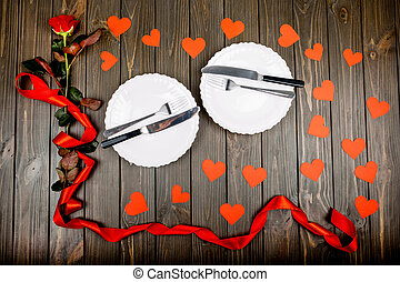 plates with cutlery and a red rose with a ribbon lie on...