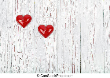 two red hearts lie on a white wooden surface